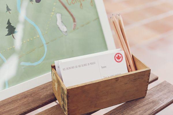 """Confetis de colores y pompones de papel, unos tote bag personalizados, una pequeña pero deliciosa mesa de dulces, un """"tocador"""" para retocar el maquillaje de las invitados. Mesa de las postales. La ilustración de un mapa de Canadá precedido de un cartel indicaba a los invitados la ruta que los novios seguirían en su luna de miel por este país. La idea era que cada invitado escogiera una de las paradas de ese recorrido para que, una vez allí, los novios le enviaran una postal. ¡Preciosa idea!"""