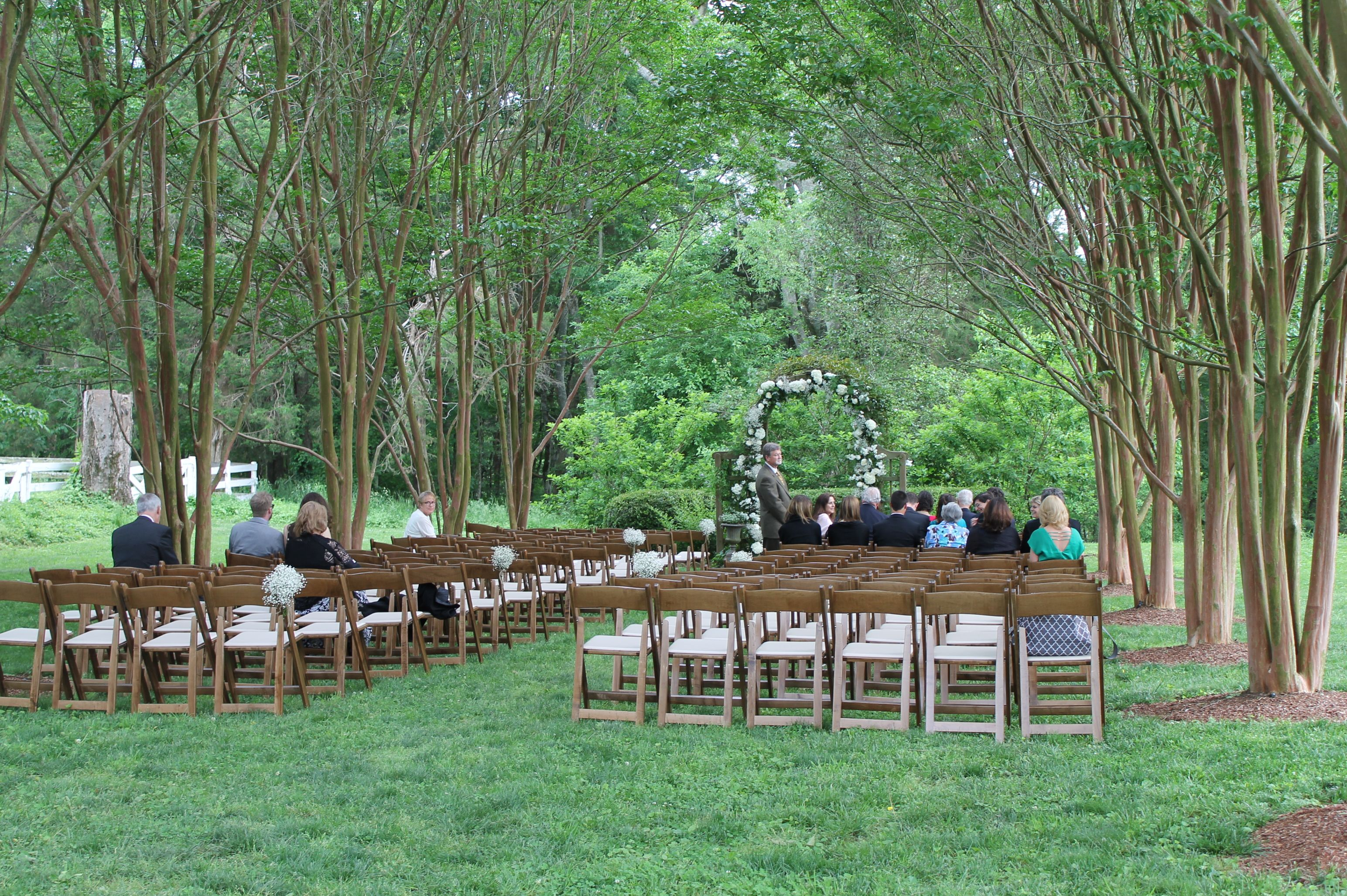 Rent E Quip s natural wood folding chairs setup for a ceremony at