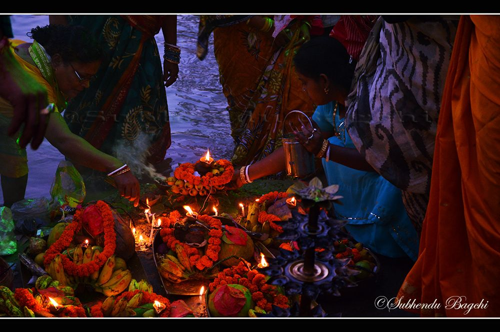 Ultimately it was the time of worshiping Sun, as god. They were re-arranging the fruits, diyas and those incense sticks for the worship.