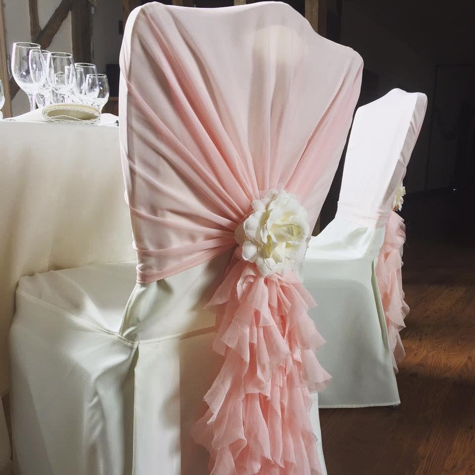 Pink chiffon ruffle chair hood with ivory rose brooch.