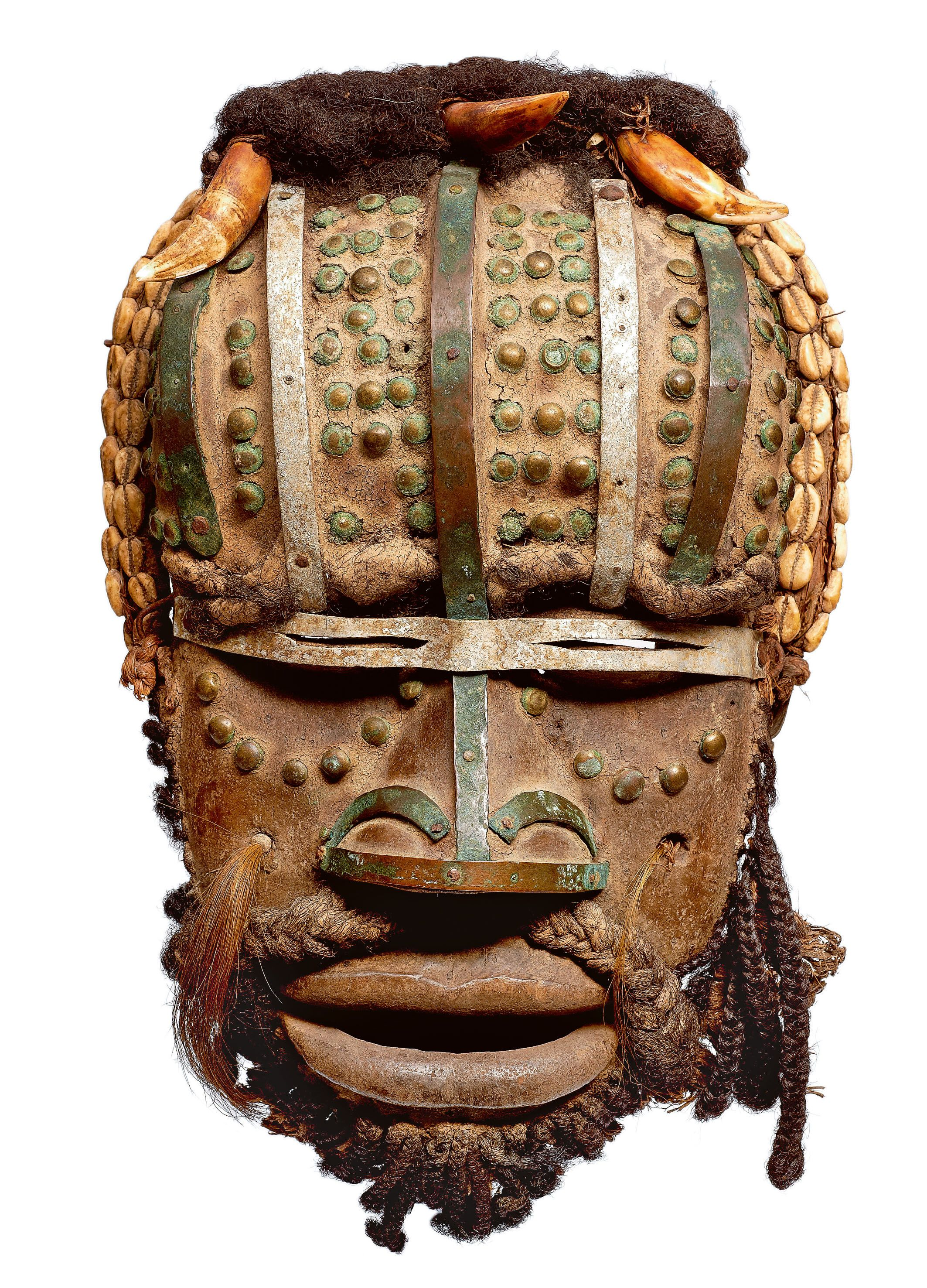 Africa   A Grebo mask, Ivory Coast/Liberia   In former times, the grè - mask of war - was supposed to encourage the warriors and to scare away the enemy sorcerer; it's now present during the funeral. All the features are emphasized to terrify: huge mouth in the shape of a muzzle, the fangs of wild animals, horns and brass mails.