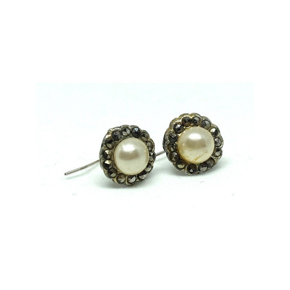 """Antique Edwardian (1901-1914) earrings featuring faux pearl and marcasite stones set into a silver setting. Marcasites are Pyrite also known as Fools Gold. It was used in jewellery due to it's ability to catch the light, giving a diamond effect. These pretty round earrings are elegant in design and sit comfortably on the ear without dropping. The wire and the earring setting at silver.  MEASUREMENTS The earrings measure 1cm / 0.4"""" in diameter.  CONDITION The earrings are in go..."""