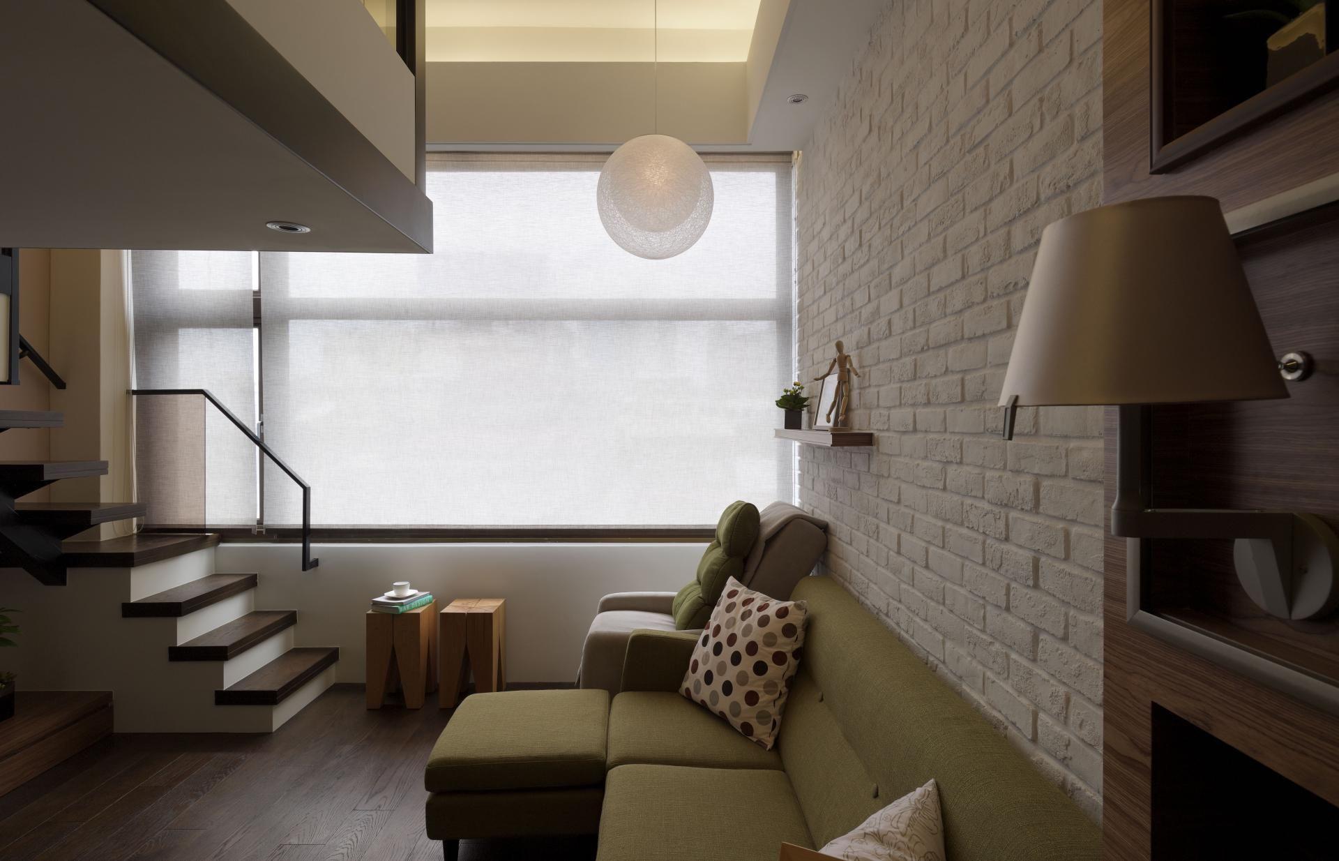沙發背牆運用了帶有休閒風的文化磚,營造出舒適的居家氛圍。圓形吊燈是用砂質包覆著,半透光的感覺柔化光線,讓室內空間散發出浪漫的感覺。