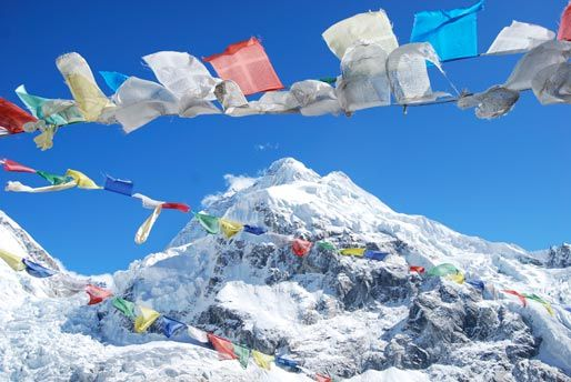 prayer flags flapping in the wind with mount everest in the background