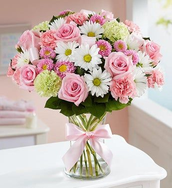 A precious baby girl has arrived and you couldn't be happier! Surprise the proud new parents with our perfectly-girly pink bouquet. Designed inside a glass vase finished with pink ribbon accents, it's a sweet way to welcome their little bundle of joy into the world. All-around arrangement with pink roses, carnations, mini carnations and Matsumoto asters; lime green carnations; white daisy poms; accented with salal tips Artistically designed in a clear glass vase accented with pink ribbon; measur