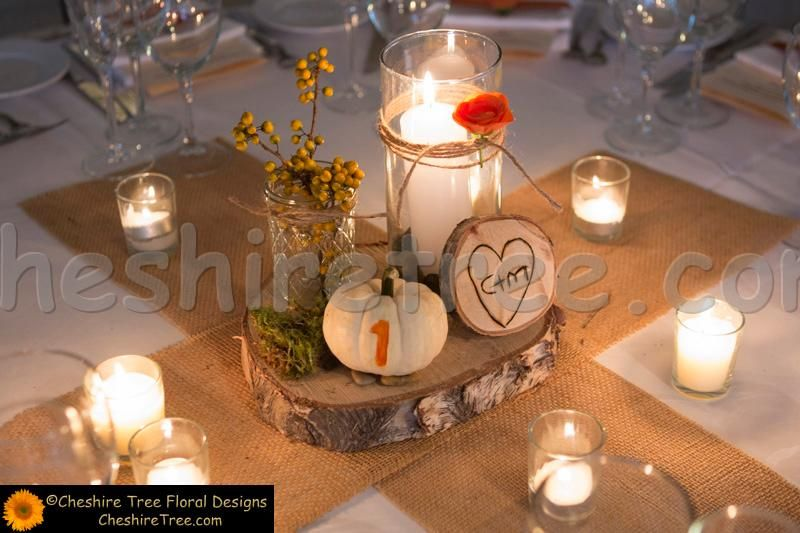 Rustic centerpieces with pillar candle and flowers the