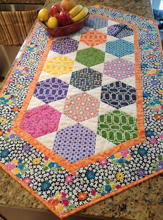 "Happy Hexie Table Runner: 29"" x 54"". Uses the Creative Grids T60 Ruler to cut both hexagons and triangles. Pattern # CLPDKR001"