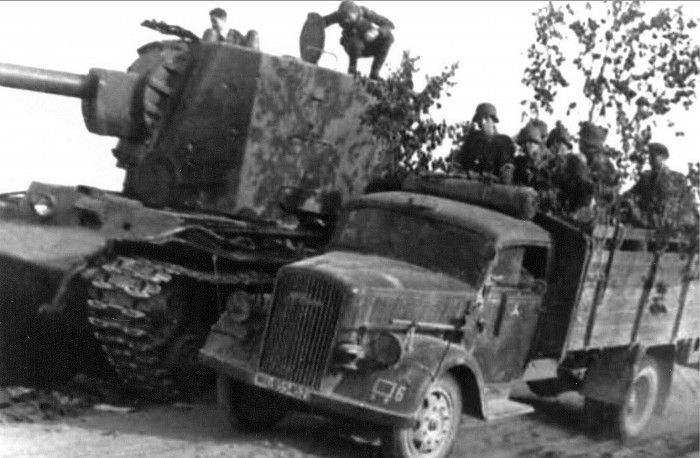 Truck Opel Blitz 3.6S, carrying German infantry, drives past a destroyed Soviet KV-2 tank.