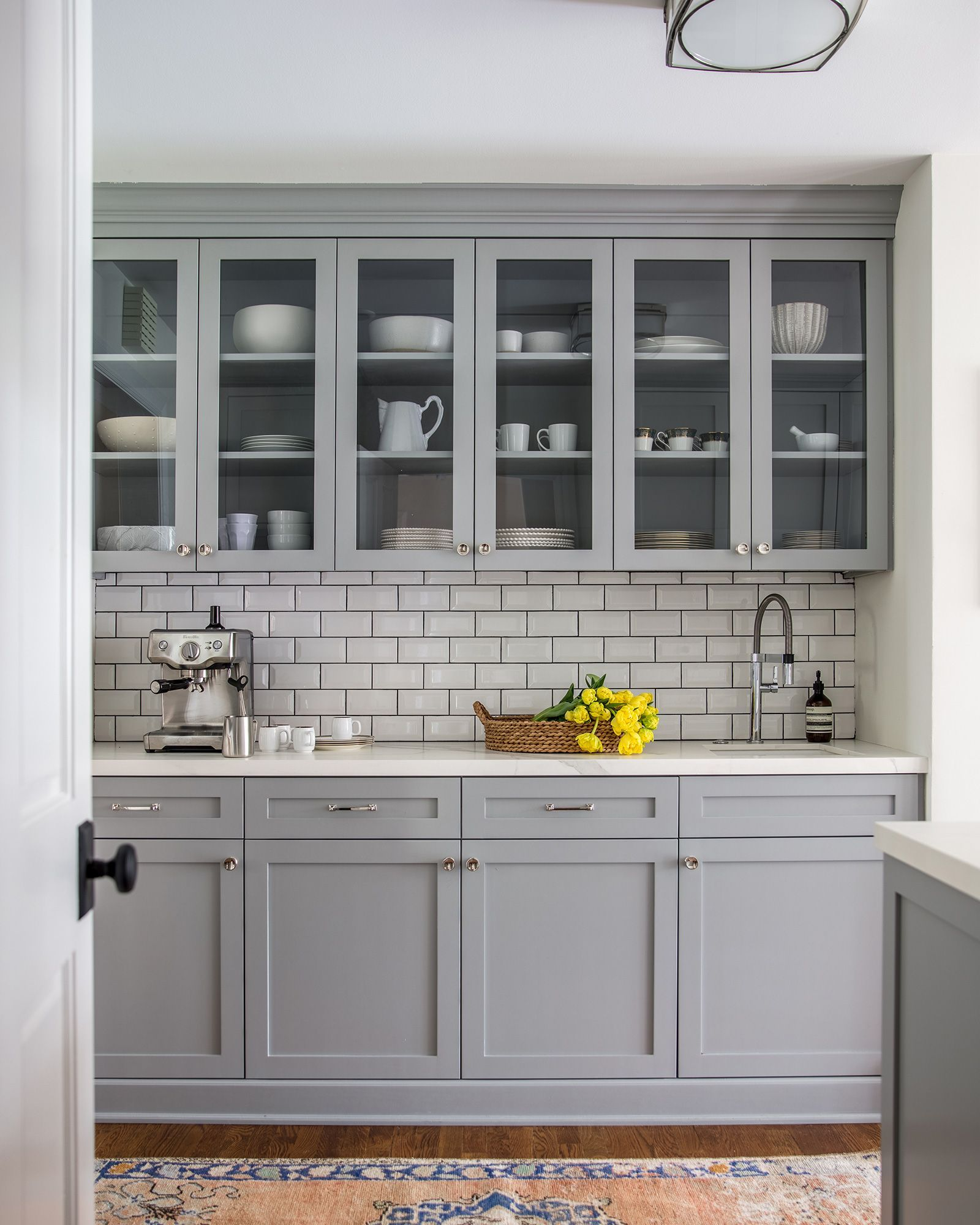 Blue Gray Cabinetry In The Kitchen With White Subway Tile And Dark
