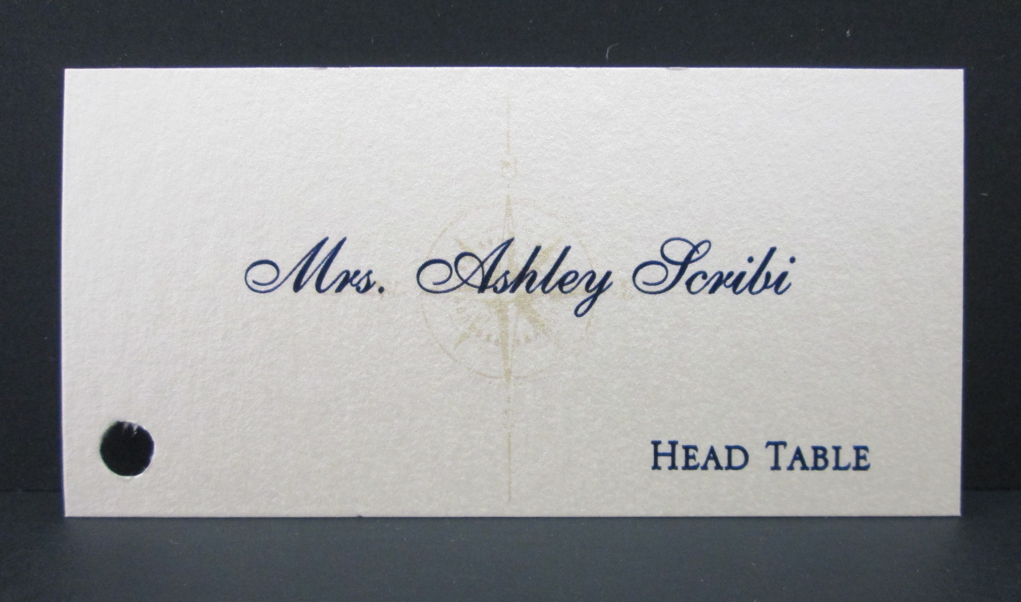 Flat place card with hole punched to attach to favor