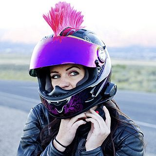 Girl Fastening Motorcycle Helmet With Hot Pink Mohawk