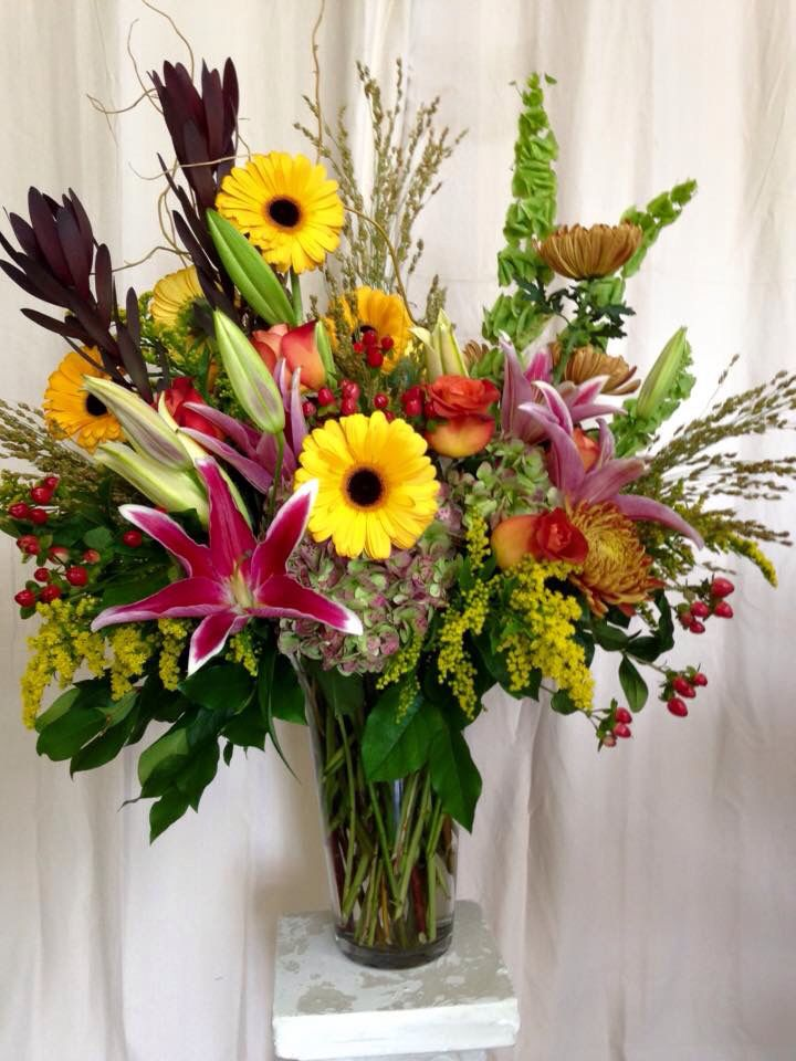 Who doesn't love a combination of daisies, roses, and lilies? Add in the blend of rich and bright floral accents and you have an arrangement perfect for the fall season.