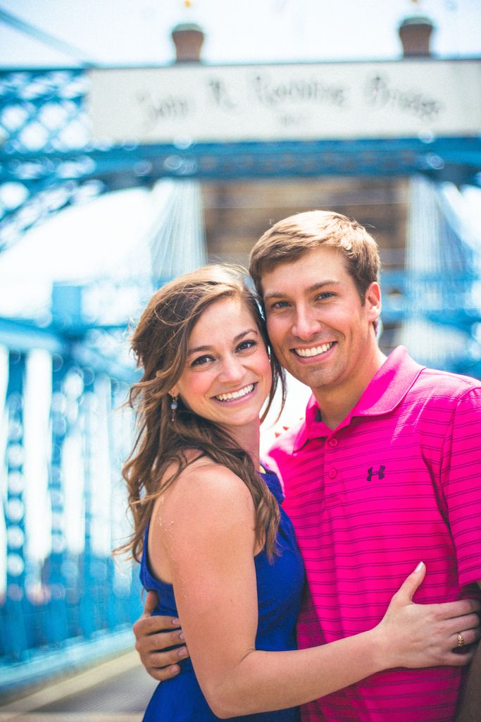Creative engagement photos on the Roebling bridge downtown Cincinnati. Cute fun couple in blue and pink take outdoor photos smiling and laughing. Great ideas for engagement session photography and poses