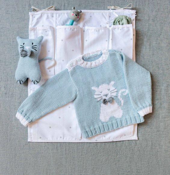 Plongez dans un univers de douceur avec ce pull et son petit motif chat. Réalisé en Laine PARTNER 3.5 coloris ciel, blanc et acier. Modèle n°3 du livre tricot n°853 : Layette chic et raffinée