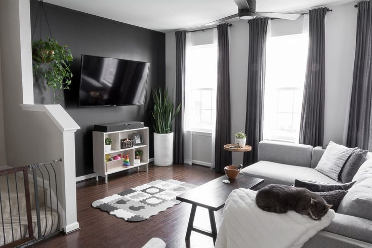 Simple, modern living room. Our modern minimal townhouse for a family of three (and two kitties!). Looking for townhouse decorating ideas? Check out our home tour. #townhomes #townhouse #townhousedecoratingideas #townhouseideas #modernhomedecorlivingroom #modernhomedecor #kidfriendlyhome #townhouseinspiration #townhomelayout #townhouselayout #modernhomedecor #nordicinspired #scandanavianinspired #houseplants #hangingplants #livingroom #openlivingspace