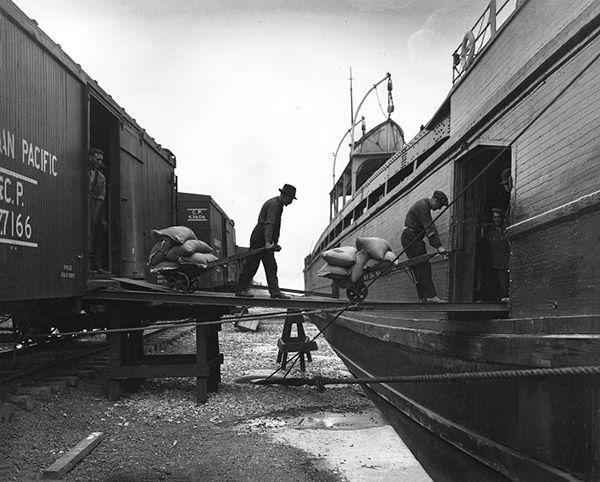 Chargement de sacs de grain sur un bateau au port deMontréal, vers 1920.