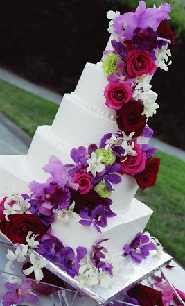 Beautiful jewel-toned flowers on this wedding cake.