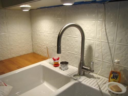 tin ceiling tiles as kitchen backsplash with farm sink and butcher