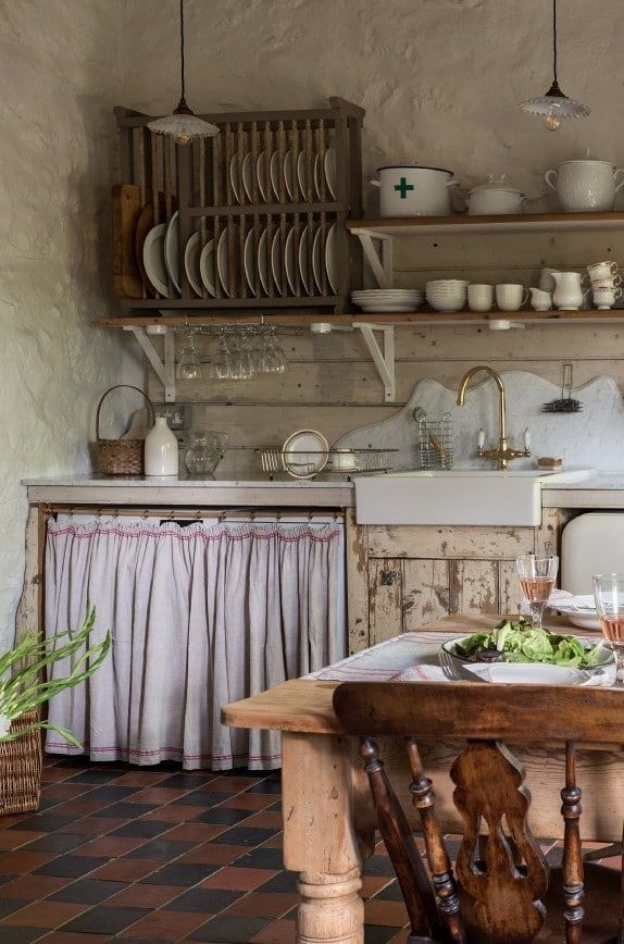 Modern Rustic decorating ideas - simple, modern country interiors to inspire you #plateracks how cute is this rustic country farmhouse kitchen with open shelves, terracotta tile floor, linen cupboard curtain, wooden plate rack, farmhouse table and reclaimed wooden units? Click through for…More #plateracks
