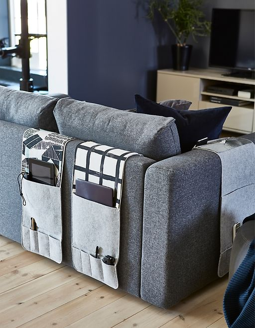 Want a sofa organiser? KNALLBÅGE from IKEA is a grey felt hanging organiser for accessories with pockets for remotes, magazines and more. It can drape over the arms or back of your sofa.