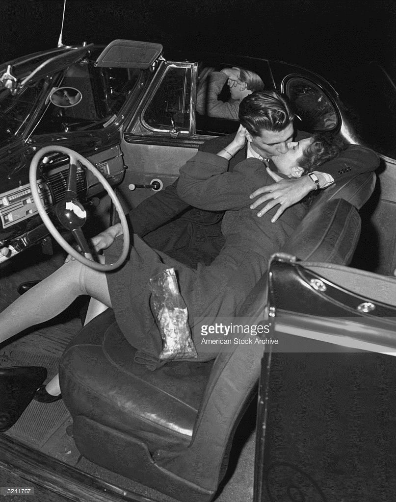 A couple kissing in the front seat of a convertible car at a drive-in movie theater, 1940s. The man in the next car ignores the couple, resting his elbow on the window.