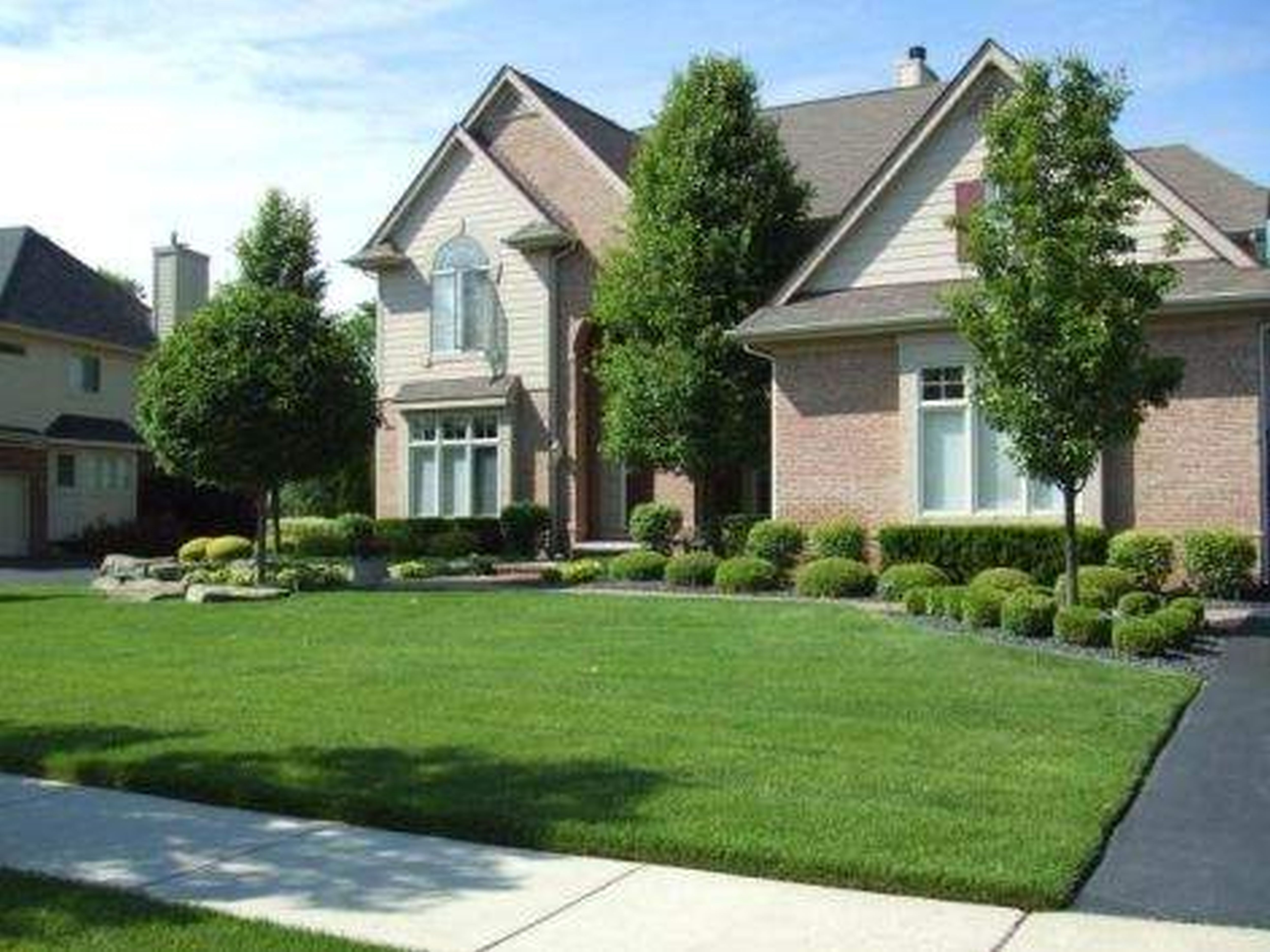 green gr feat green plants and trees in front of brown brick ... on ranch style home landscape design, colonial home landscape design, victorian house landscape design,
