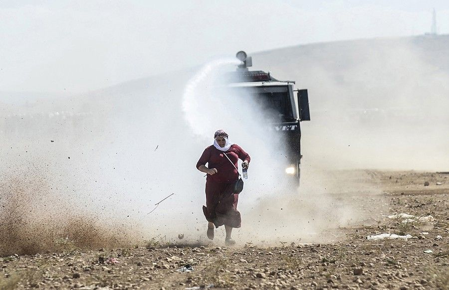 A Kurdish woman runs away from a water cannon during clashes with Turkish soldiers near the Syrian border after Turkish authorities temporarily closed the border, preventing Syrian Kurds who had accompanied their families to safety inside Turkey, from returning to the battlefront, on September 22, 2014. (Bülent Kılıç/AFP)