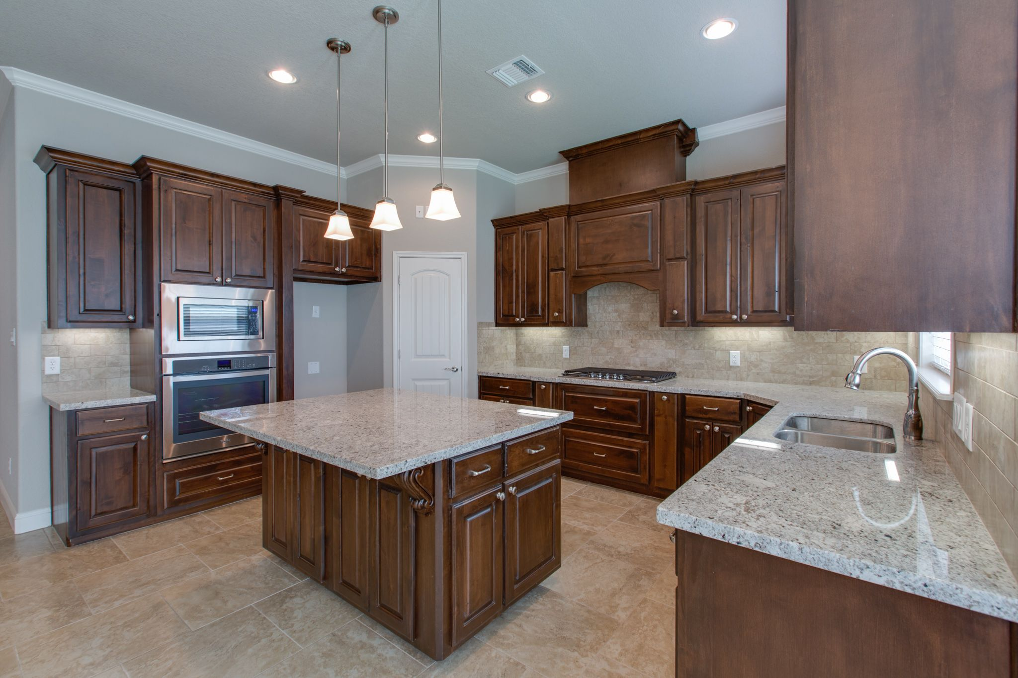 kitchen with knotty alder cabinets light granite and tumbled