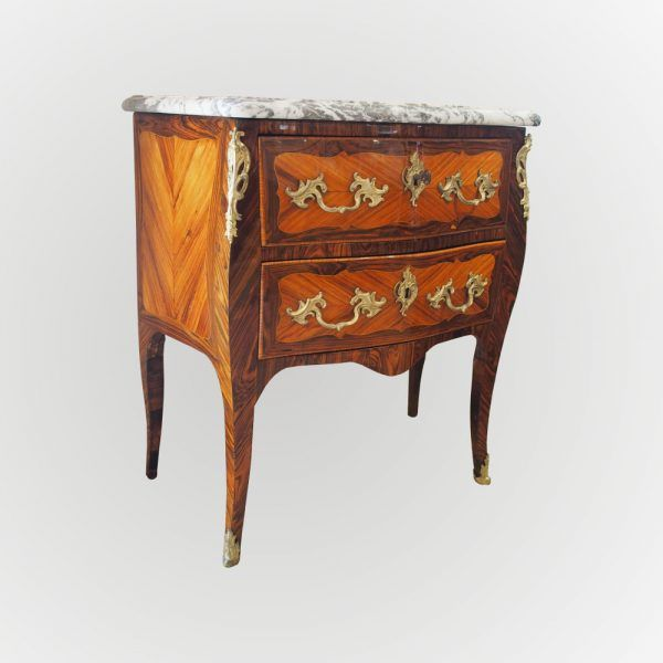 Commode sauteuse d'entre deux, d'époque Louis XV, ouvrante par deux tiroirs, reposant sur des pieds galbés se terminant par des sabots en bronze doré. La Façade est galbée et les cotés en fuite, cette commode datant du XVIIIe est marquetée de bois de rose dans des encadrements de bois de violette avec des filets de buis.