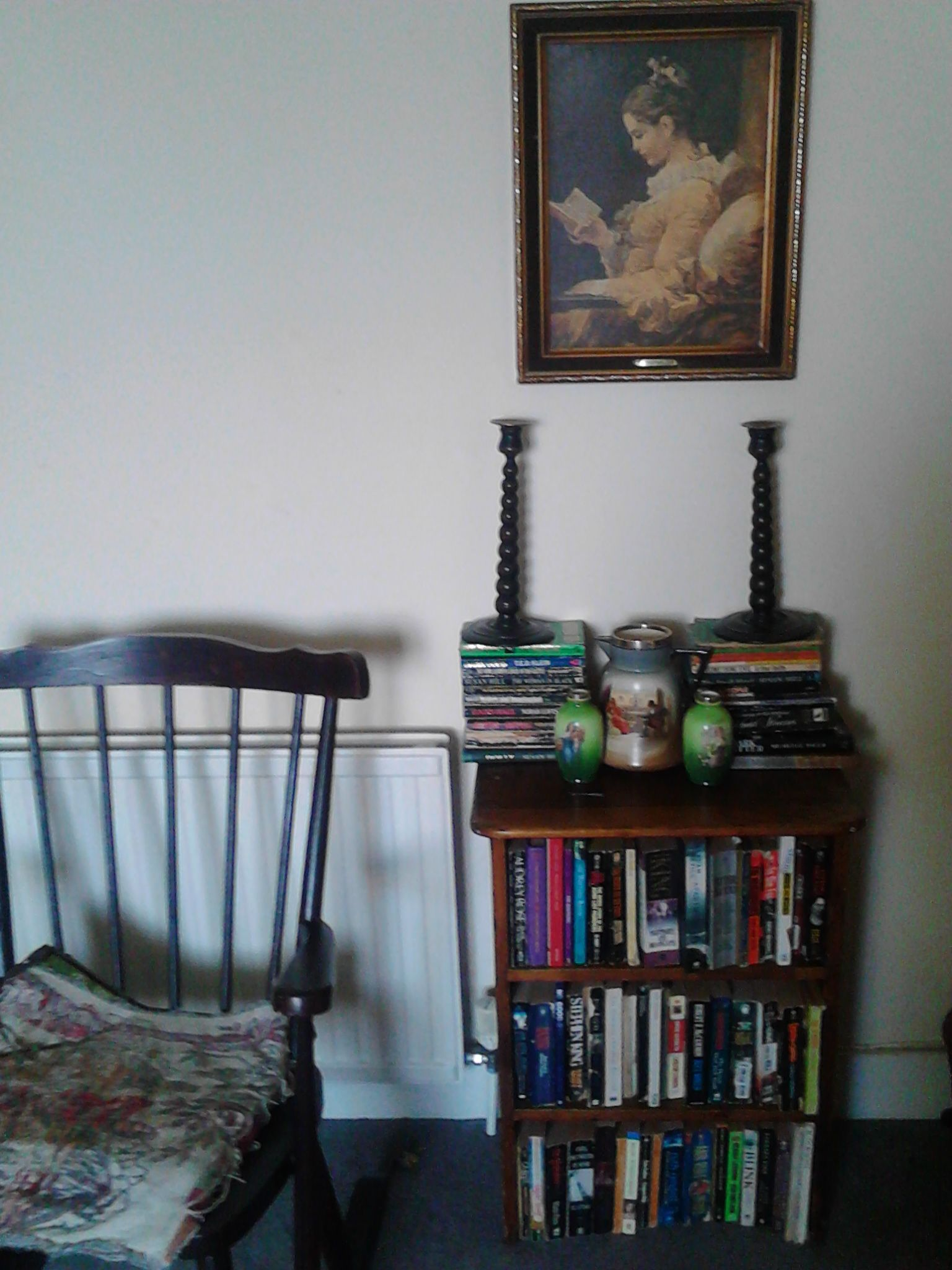 reading corner with stained vintage rocking-chair, Victorian candlesticks and Victorian silver-topped picture vases