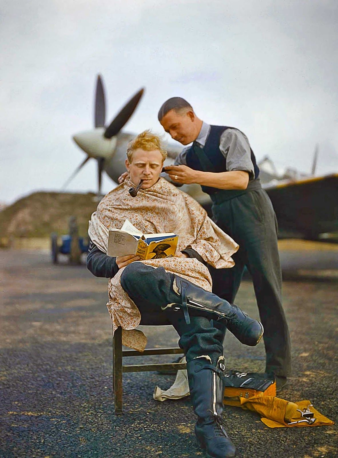 A pilot at Fairlop airfield in Essex has a haircut during a break between sweeps. A Supermarine Spitfire is in the background. 1942.