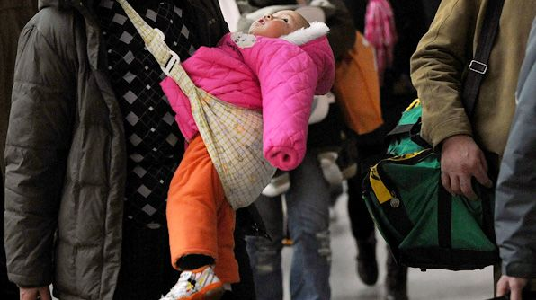 A mother carries her baby to board a train at the Wuchang Railway Station in Wuhan of Hubei Province, China.
