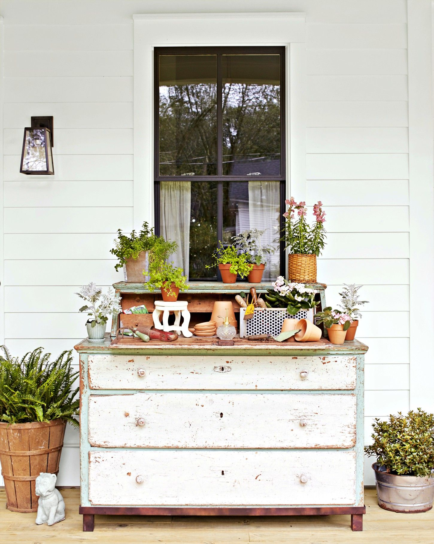 Dresser on the porch used for a potting bench and tool storage