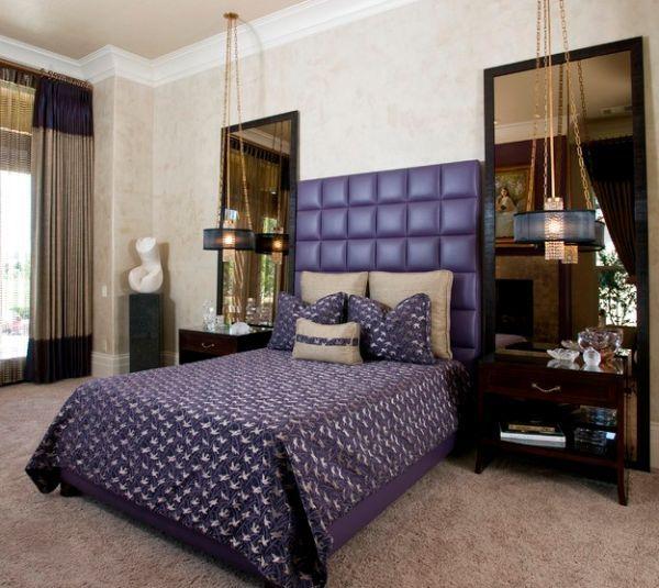 Getuftetes lila Kopfteil und interessante Belichtung geben diesem Hauptschlafzimmer
