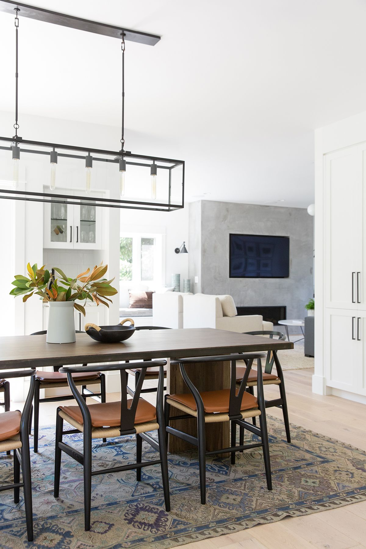 Modern light airy dining room connection to kitchen with wishbone chairs wood table modern art and vintage rug studio mcgee design blog