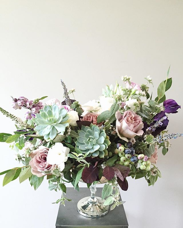 antique purple floral centerpiece of succulents, amnesia roses, sweet peas, delphinium, lavender, blueberries, mountain mint, cotinus, quicksand roses, majolika roses, and veronica in silver compote | arranged by Lori Tran of Wild Green Yonder