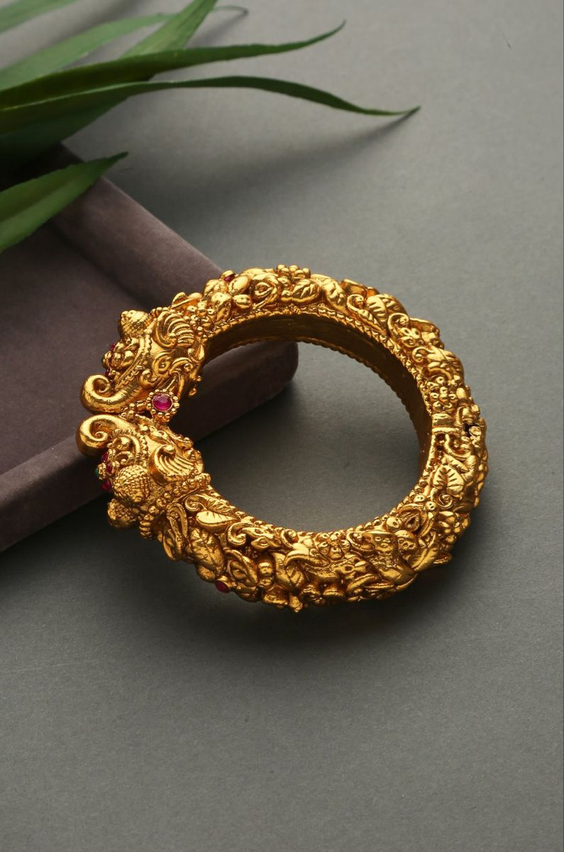 Gold Plated South IndianTemple Work Emboss Bangles with Floral Motifs. Closure - Screw.Intricacies of South Indian temples now in your jewellery wardrobe. Based on silverand copper alloy, emboss work studded with high grade stones and plated with 24k gheru gold. South Gold never looked more authentic.STYLE TIP - St