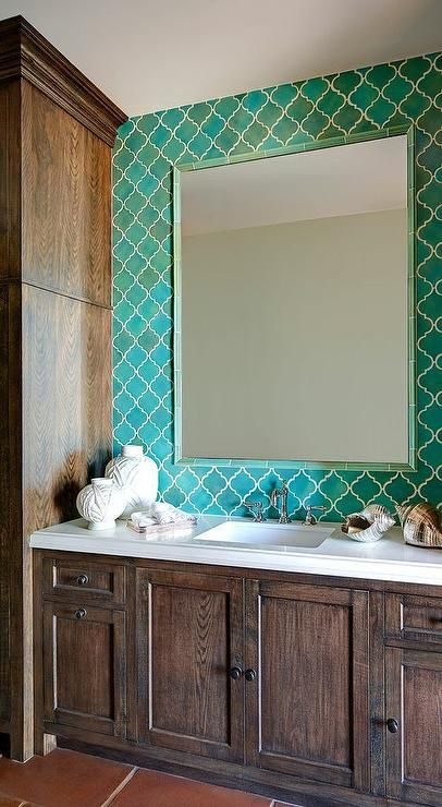 Brown and blue bathroom features a wall tiled in turquoise Moroccan tiles lined with a turquoise tiled mirror placed above a dark brown stained oak vanity topped with white quartz fitted with a white porcelain sink and vintage style faucet flanked by floor to ceiling cabinets.