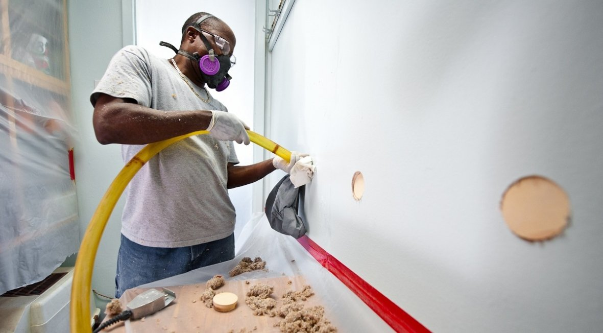 Photo Of A Man Blowing Insulation Into A Hole Drilled Into A Wall Home Insulation Blown In Insulation Interior Wall Insulation