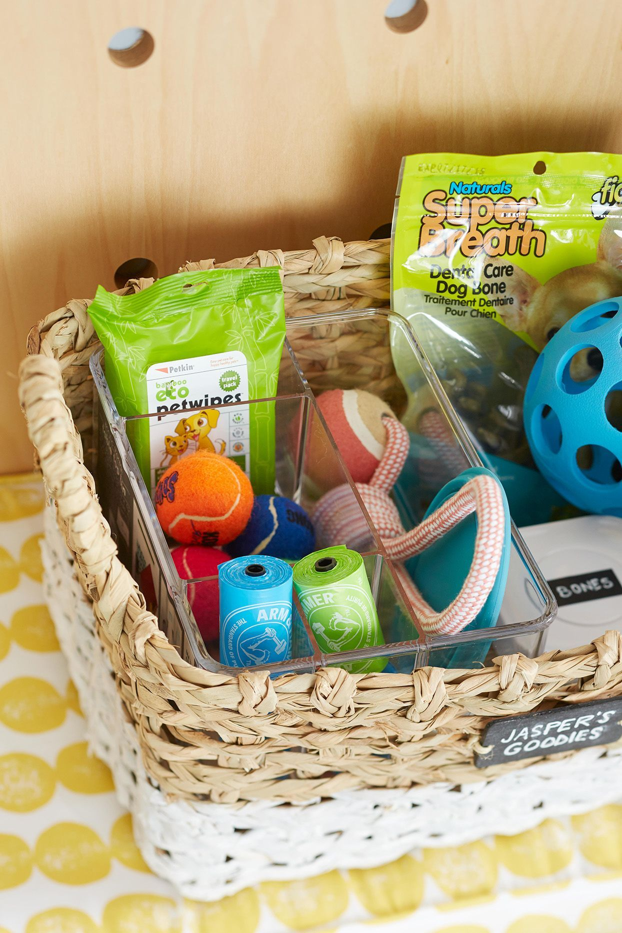 Keep an open bin or basket near floor level to promote daily play and keep toys within your pet's reach. This also helps reinforce which toys are for your pets and which are for other members of the family. #petstorageideas #storageandorganizationideas #petsuppliesorganization #dog #cat #petparent #bhg