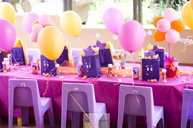 Dora party colors and balloons on the back of each chair Dora