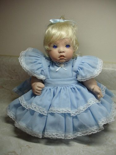 This is a hand crafted porcelain DOLL made by me.      Doll limbs are completely movable allowing doll to sit or lay straight.  Blue dress is beautifully finished.   An exquisite treasure you will own.