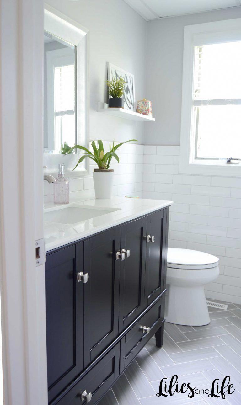 Modern white bathroom with black vanity, gray herringbone ...