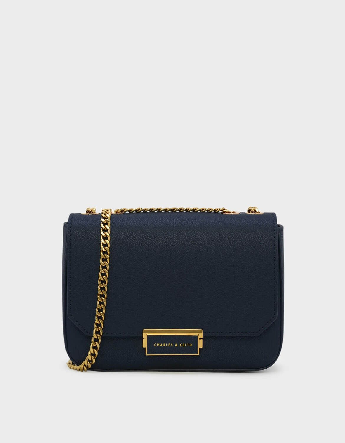 15a1c18450f CHARLES   KEITH - Bags. Navy crossbody bag featuring a front flap and a  push-lock closure. Comes with a long chain.