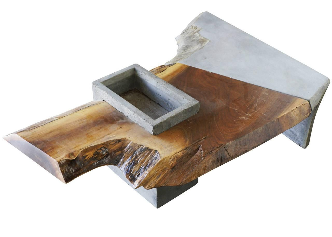 Custom-made Brutalist concrete and driftwood coffee table featuring a unique asymmetric design with textured edges. In the center is a concrete