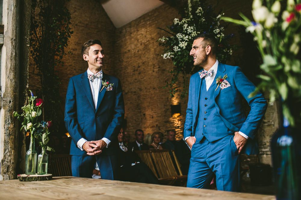 Groom wears a blue suits from Reiss - Image by Samuel Docker Photography - Claire Pettibone lace dress in a rustic barn wedding in the Cotswolds with red bridesmaid dresses. Groom wears a Reiss Suit with floral bow tie and light up letters decoration.