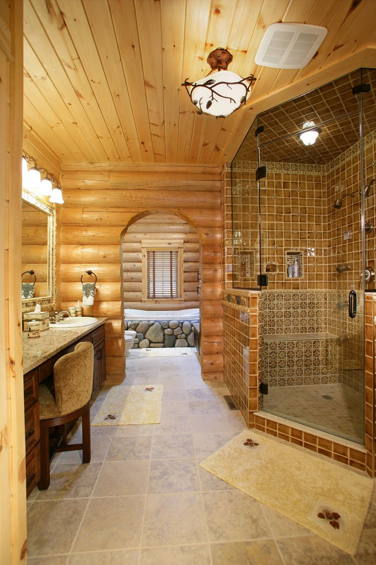 I love many things about this log home bathroom- the river stones ...