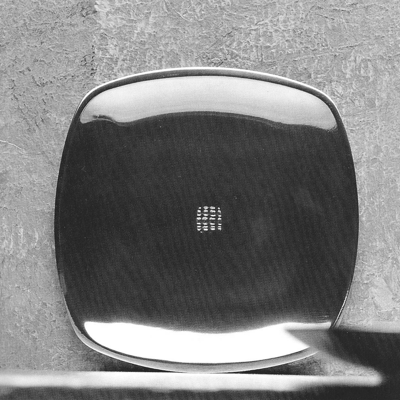 Piatto Zen carré in alluminio con timbro a rilievo in centro. Il bordo presenta una lieve smussatura che crea un gioco di luce particolare. Design di STRA-DE STRATEGIC-DESIGN.