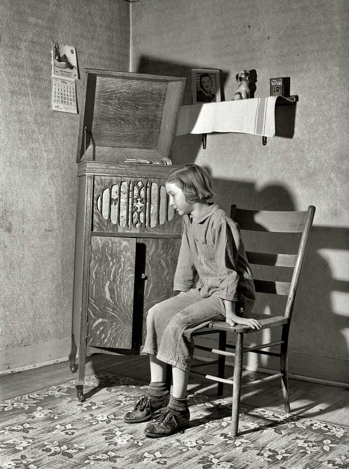 Photo of The daughter of a borrower farmer listens to a phonograph. Cro …