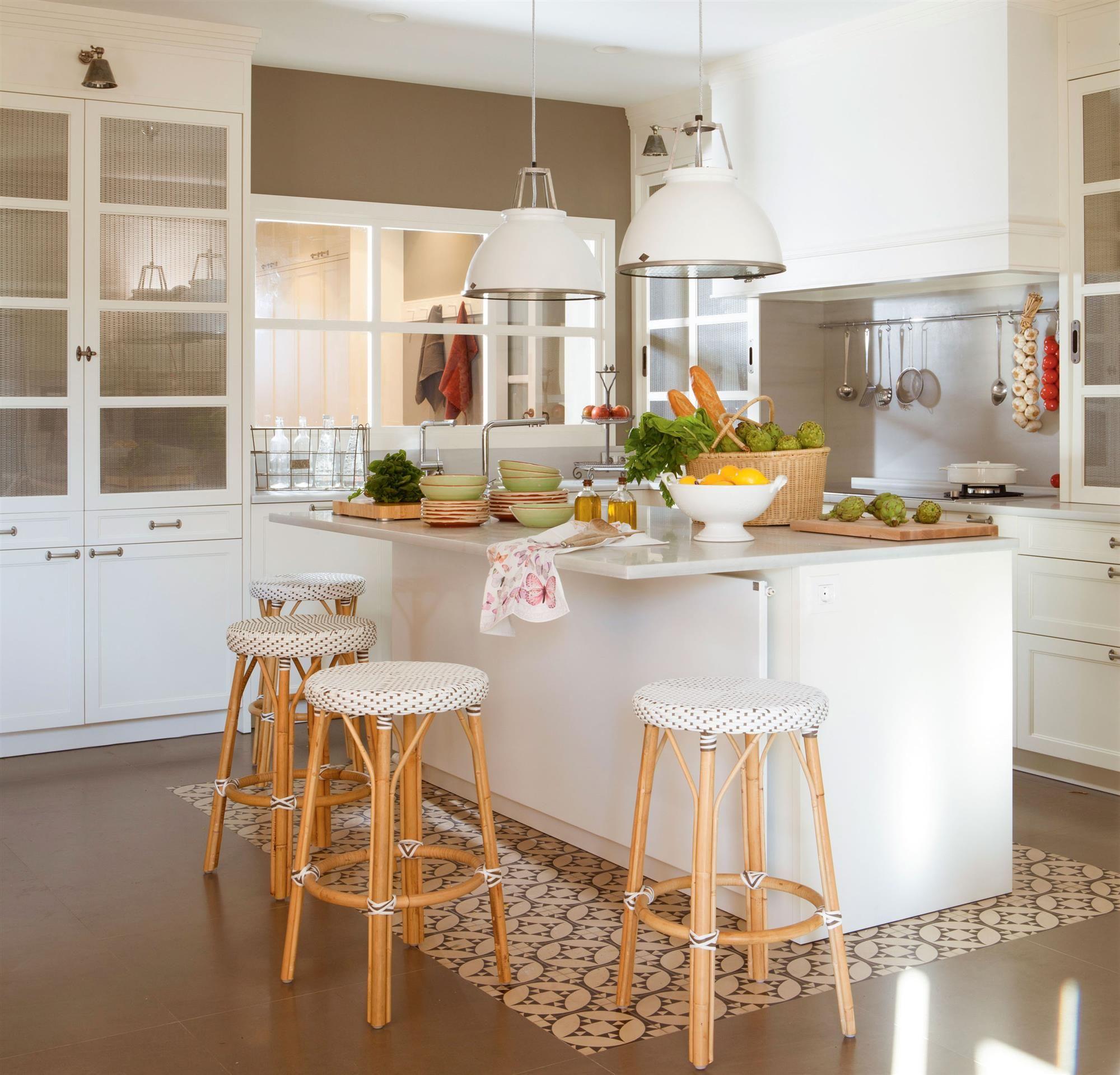 Cocina blanca con isla sobre suelo hidraulico y taburetes de ...